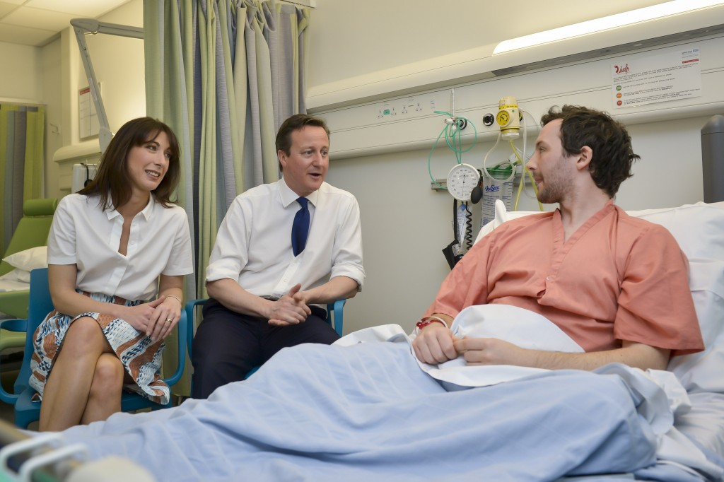 Prime Minister David Cameron and his wife Samantha Cameron talk with patient Tom Lawrence (right), 30, from Manchester, at his bedside, during a visit to the Salford Royal Hospital in Manchester, before speaking at the Conservative Spring Forum.